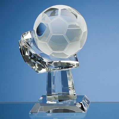 10CM OPTICAL GLASS FOOTBALL MOUNTED ON HAND AWARD.